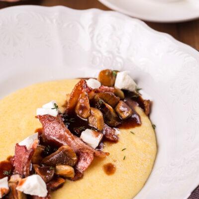 Полента з солоним сиром, білими грибами та беконом